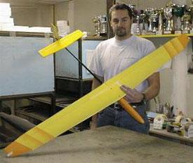 planeur radiocommandé Nuaj Aeromod jaune et orange, porté par Aexis Maréchal, dans l'atelier