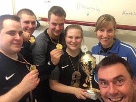 Teamselfi mit der Goldmedaille und dem Pokal