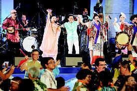 第6回世界のウチナーンチュ大会開会式の最後に「てぃんさぐぬ花」を歌う夏川りみさん(左より2人目)と具志堅用高氏(左より3人目)。舞台下左は翁長知事=27日夜、那覇市の沖縄セルラースタジアム那覇
