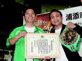 市民栄誉賞、チャンピオンベルトを掲げる比嘉選手(右)と松本浦添市長=9日、浦添市役所