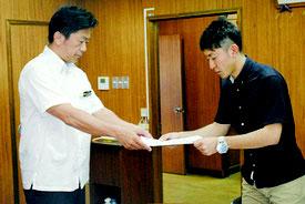 陸自配備計画に関し、中山市長に抗議文を手渡す嵩田公民館の川満起史さん=15日午後、市役所