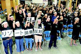 リゾート建設阻止に向け、「守ろう」と三唱する竹富島の島民=28日夜、竹富島まちなみ館