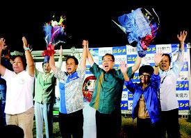 5期目の当選を決め、比例で当選した公明の遠山清彦氏とともにバンザイ三唱する西銘恒三郎氏(中央)=23日未明、選対本部