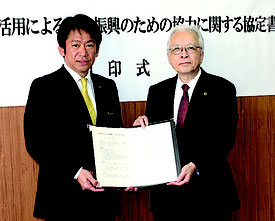 知的財産の活用による産業振興のための協力に関する協定を結んだ中山市長(左)と渡邉会長=13日、市役所庁議室