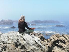 sentada na rocha frente ao mar a meditar