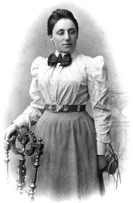 Emmy Noether steht vor einem Stuhl. Die junge Frau trägt Bluse, Kleid und eine markante Fliege.