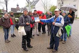Sebastian Olschewski (links) und Jürgen Schnepf sowie eine ziemlich durchgeweichte Exkursionsgruppe