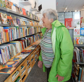 A passenger stands in front of shelves of hundreds of children's books in the gift shop
