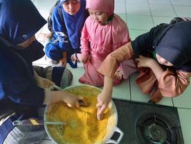 収穫したウコンを粉末にする教員と児童
