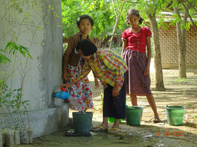 新設した雨水タンクより、散水用の水を汲む子どもたち。