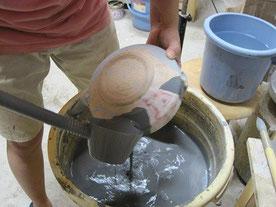 陶芸の作業工程のひとつ、薬がけ。絵付けした素焼生地に蝋を塗り撥水作用を施し、織部釉を柄杓で流し掛け、窓絵にしている。青織部という