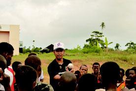 生れて初めて野球ボールを見るザンジバルの青少年らに野球を紹介する上原さん=2014年9月、アフリカのタンザニア国ザンジバル島(提供写真)