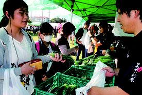 「特産島ごちそう祭」で、石垣島産の野菜を買い求める市民=25日午前、市健康福祉センター中庭