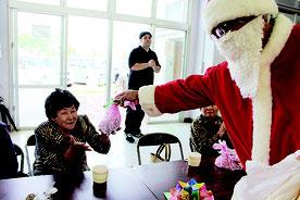 サンタクロースが登場し利用者にプレゼントを配った=19日、大川公民館