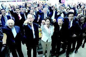 ガンバロ―三唱する諸見里氏(写真前列左から3人目)。東門氏(同右から3人目)や知事を支える国会議員や県議、市議らが詰めかけた=16日、沖縄市安慶田の選対事務所