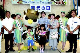 「2017人目」に選ばれた田嶋さんファミリーと関係者ら=1日、南ぬ島石垣空港