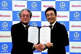協定書にサインし握手を交わす外間町長(左)と齋藤部長=6日、石垣市健康福祉センター