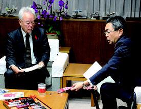 米軍から借りた部品を見せて説明する中嶋局長(右)と説明を受ける富川副知事。落下物にはなかったリボンが実物にはある=11日夜、県庁