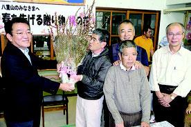 JTA八重山営業所の黒島所長(左端)から桃の花が贈呈された=23日午前、八重山育成園
