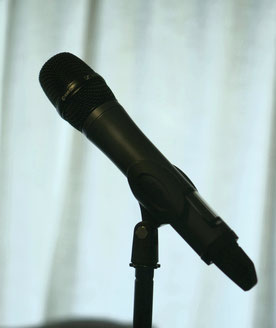 Wireless handheld microphone on a stand with shallow focus and the background blurred.
