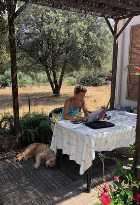 Die Puppenfee sitzt auf der Terrasse mit dem Laptop, schreibt ihren Blog und neben ihr liegt der Hund und schläft.