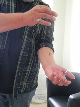 Mit einem Pendel wird eine Testung am Unterarm eines Mannes durchgeführt.