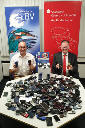 Da ist ganz schön was zusammengekommen: Volker Woitzik und Sparkassenvorstand Dr. Martin Faber mit den alten Handys, die nun recycelt werden.