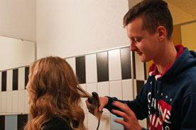 Ein Coiffeur macht bei einer Frau die Haare