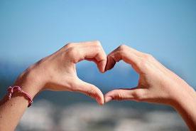 Hände formen Finger zu Herz.