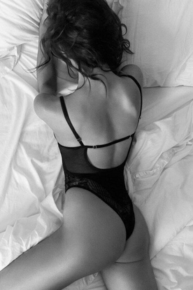 Vrouw in sexy teddy / body in bed. Zwart wit foto