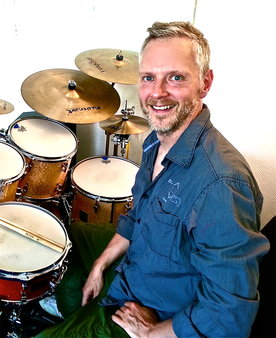Christian Glieber sitzt am Schlagzeug und dreht sich lächelnd zur Kamera.