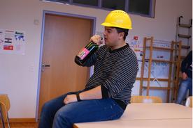 Ein Bauarbeiter trinkt während der Arbeit Alkohol.
