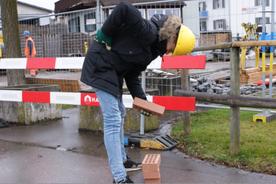 Ein Bauarbeiter mit einer falschen Haltung beim Heben von Lasten.