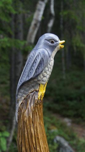 Vogel aus Holz sitzt auf Wanderstab im Wald