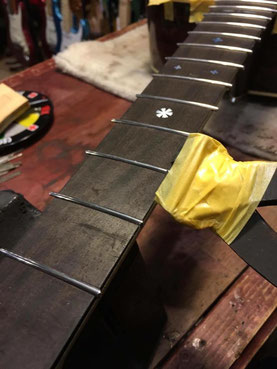 ギターネックの新しいステンレスフレットをカットしている作業