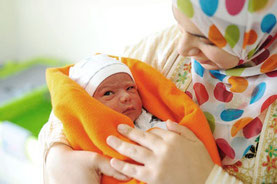 Frau mit Kopftuch und Säugling