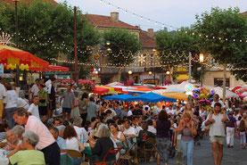 Déguster les produit locaux au marché de nuit de Vic-Fezensac dans le Gers, en Occitanie, à 5 minutes de Lassenat éco-maison d'Hôtes en Gascogne, chambre d'Hôtes de charme, table d'hôtes gourmande, bio et locavore, destination campagne, écotourisme.