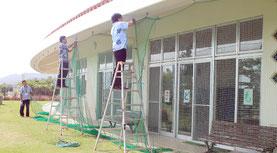 石垣市健康福祉センターで、ガラスをネットで覆う台風対策をする職員=7日午後4時ごろ