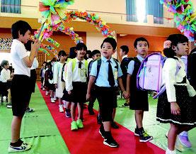新1年生が入場し、花道で歓迎する在校生=10日、新川小学校