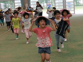 走って避難する平真小学校の児童ら=22日午前、石垣市中央運動公園内