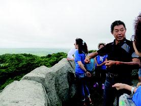 台湾移民が入植した名蔵地区について、一行に説明する王滝さん=21日午前、バンナ公園