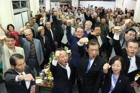桑江氏(前列右から3人目)のあいさつの後、ガンバロー三唱をする関係者ら=17日、コザ十字路前の事務所