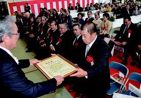 与那国町の町制施行70周年式典で外間庁長が73個人3団体を表彰した=2日、離島総合振興センター