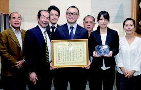 石橋医師(中央)が竹富町に受賞報告を行った=15日、竹富町役場