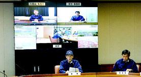 今回の会議は、県庁と宮古・石垣を生中継で結び、会議を行った。議長の翁長知事(写真中央)後ろのモニターには、両島の様子や両事務所長が映し出された=11日、県庁