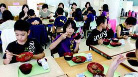 給食では「クーブイリチー」などが出され、児童らは伝統の味に笑顔を見せた=15日、曙小学校