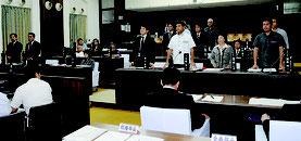 ヘリパッド反対派を批判する意見書に起立して賛成する与党(右側)=24日午前、議場