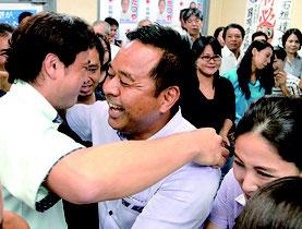 支持者らと抱擁を交わす石垣氏(中央)=9日夜、市内事務所