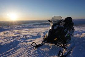 Snowmobile tour up a mountain
