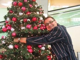 Ein Mann unarmt einen geschnückten Weihnachtsbaum